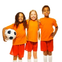 Portrait of soccer team divers looking team of little boy and girls holding prize cup and football ball smiling and cheering isolated on white